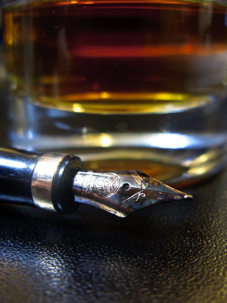 A dirty pen and whiskey in a dirty glass. Bad ideas ahead.