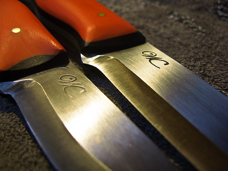 Detail of the WC Knives logo, which he hammers in with a sledge hammer and the G10 handles.