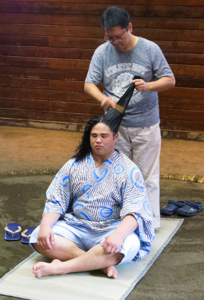 Cleaning the wrestler's hair and spreading the wax.