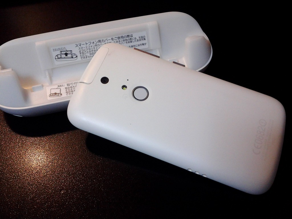 The back side with the touch-sensitive button. The three holes on the side fit the charging station.