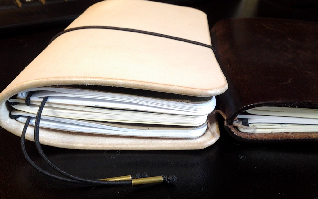 The OCW Four next to the Midori Passport sized. Both are holding three notebooks.
